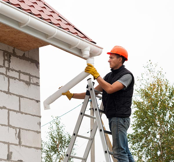 Gutter Installation — Man Installing Gutter in Delavan, WI