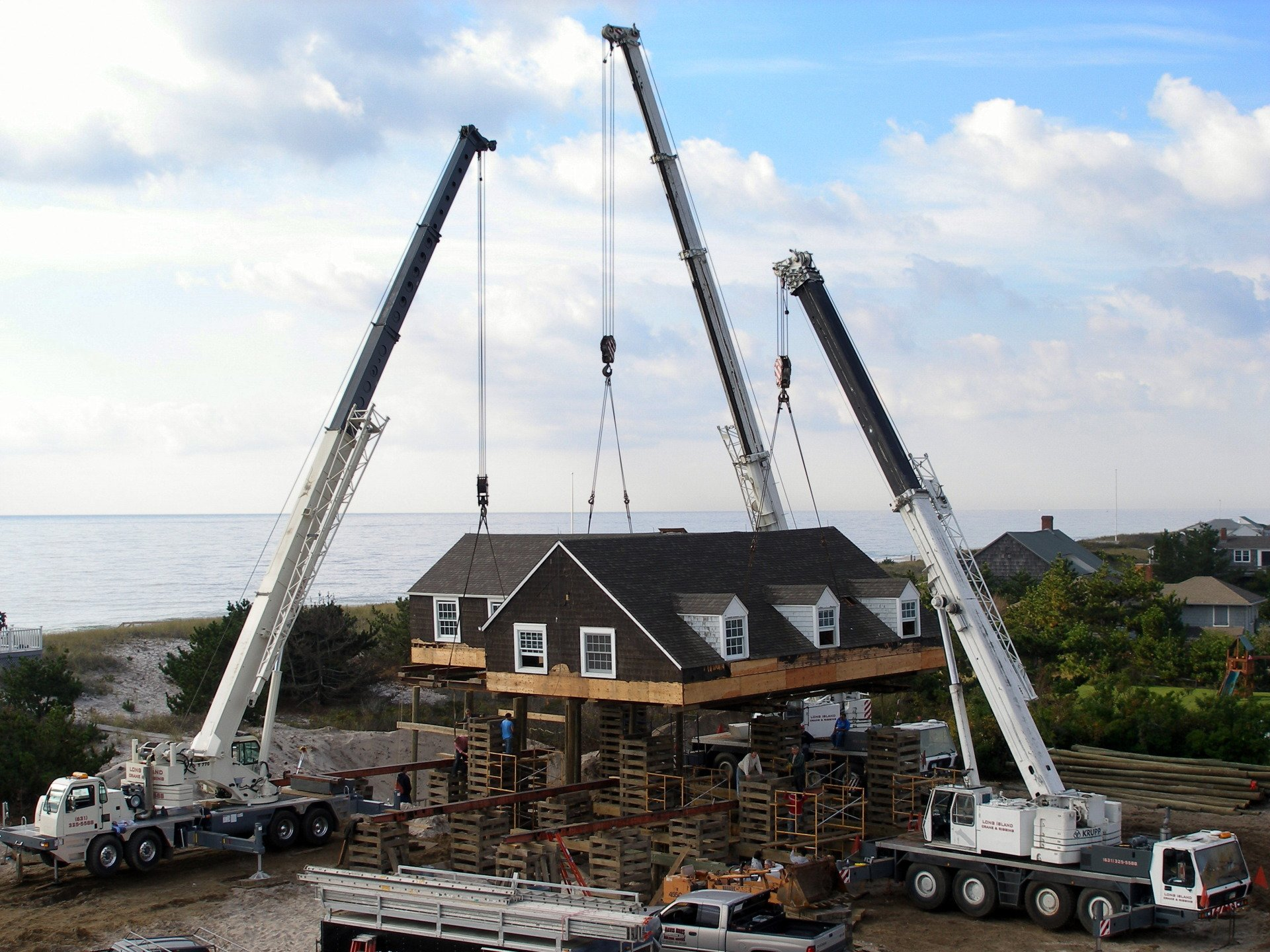 Three Cranes Setting A House Section On Its Foundation In Westhampton Beach