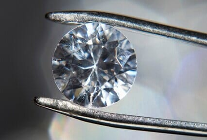 Diamond held by tweezers u2014 Custom jewelry in West Chicago IL & Engagement Rings - West Chicago IL - Gloriau0027s Jewelry
